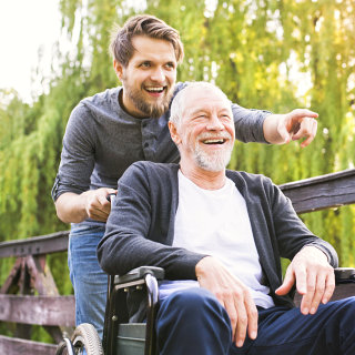 staff assisting elder man on his wheelchair
