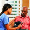 caregiver checking the blood pressure of elder man