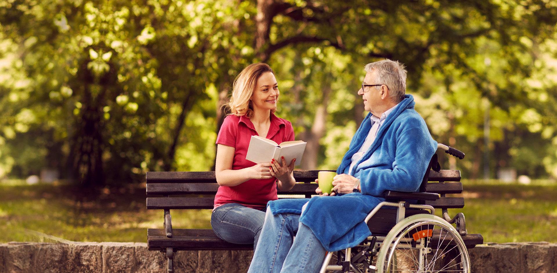 caregiver reading book for elder man
