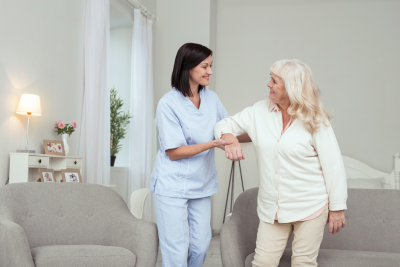 caregiver helping senior woman who smiling