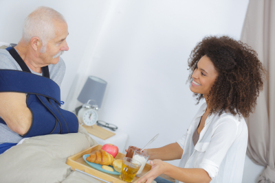 smiling female nurse serving breakfast to senior man